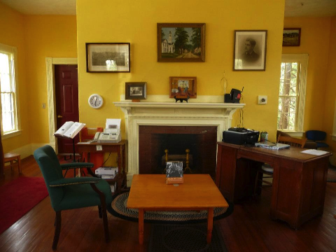Photograph of the Haydenville Library Interior showing the painted fireplace and photograph of Charles Hayden